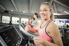 Fit woman running on the treadmill while listening music Stock Photo