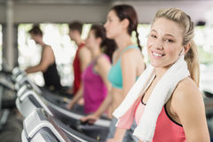 Fit woman running on the treadmill while listening music Stock Photos