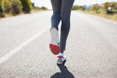 Fit woman running up the open road Stock Image