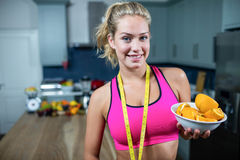 Fit woman showing a bowl of oranges Stock Photos