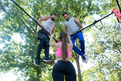 Fit woman showing thumbs up to her friends during extreme workou. Low-angle rear view of a fit women showing thumbs up to her two male friends during extreme Stock Photos