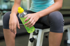 Fit woman sitting on bench holding energy drink Stock Images