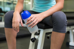 Fit woman sitting on bench holding sports bottle Stock Image