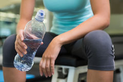 Fit woman sitting on bench holding water bottle Royalty Free Stock Photos