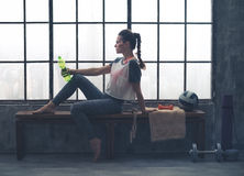 Fit woman sitting on bench in loft gym holding water bottle Royalty Free Stock Photo