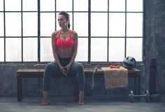 Fit woman sitting on bench in workout gear listening to music Stock Images
