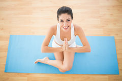 Fit woman sitting in cow face pose smiling at camera Stock Photography