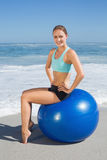 Fit woman sitting on exercise ball at the beach smiling at camera Stock Photo