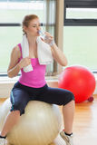 Fit woman sitting on exercise ball and drinking water Stock Photography