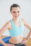Fit woman sitting on exercise ball in fitness studio Royalty Free Stock Photo