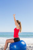 Fit woman sitting on exercise ball stretching arms Royalty Free Stock Photography