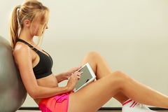 Fit woman sitting on floor with tablet pc Royalty Free Stock Images
