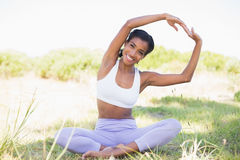 Fit woman sitting on grass in lotus pose smiling at camera Royalty Free Stock Images