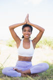Fit woman sitting on grass in lotus pose smiling at camera Stock Photo