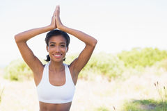 Fit woman sitting on grass in lotus pose smiling at camera Stock Photography