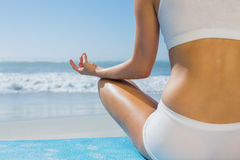 Fit woman sitting in lotus pose on the beach Royalty Free Stock Image