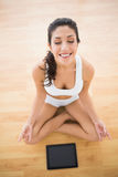 Fit woman sitting in lotus pose with her tablet pc Royalty Free Stock Photos