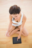 Fit woman sitting in lotus pose using her tablet pc Stock Photo