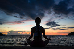 Fit woman sitting in lotus position while practicing yoga on the Stock Image