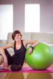 Fit woman sitting next to exercise ball Stock Photos
