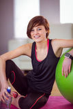 Fit woman sitting next to exercise ball Stock Image