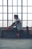 Fit woman sitting in profile in city loft gym tying shoe Royalty Free Stock Photography