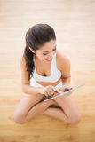 Fit woman sitting and using her tablet pc Royalty Free Stock Photography