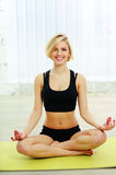 Fit woman sitting on the yoga mat and meditates Stock Images