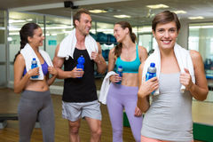 Fit woman smiling at camera in busy fitness studio Royalty Free Stock Photography