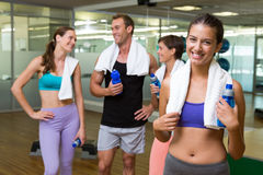 Fit woman smiling at camera in busy fitness studio Stock Image