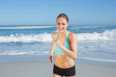 Fit woman smiling and jogging on the beach Stock Photo