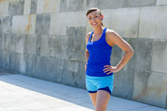 Fit woman smiling. Resting after run against the city wall. Royalty Free Stock Images