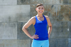 Fit woman smiling. Resting after run against the city wall. Royalty Free Stock Photo