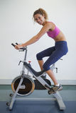 Fit woman on the spin bike smiling at camera. At the gym Stock Photo