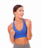Fit woman in sport clothing charmingly smiles. Charming woman wearing sport clothing smiling and looking at you on isolated background Royalty Free Stock Image
