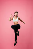 Fit woman in sport clothing jumping with left leg up Stock Image
