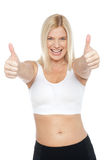 Fit woman in sports bra gesturing double thumbs up Stock Image