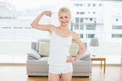 Fit woman in sportswear flexing muscles in fitness studio Royalty Free Stock Photos