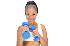 Fit woman in sportswear working out with blue dumbbells Stock Photos