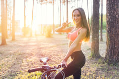 Fit woman standing with bicycle in park enjoying sunset. Stock Photo