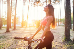 Fit woman standing with bicycle in park enjoying sunset. Stock Image