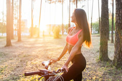 Fit woman standing with bicycle in park enjoying sunset. Royalty Free Stock Photography