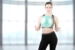 Fit Woman Standing Holding a Pilates Ball Stock Photos