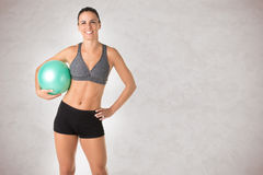 Fit Woman Standing Holding a Pilates Ball Stock Images
