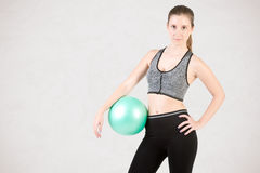 Fit Woman Standing Holding a Pilates Ball Stock Photography