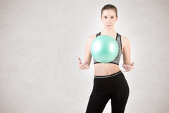 Fit Woman Standing Holding a Pilates Ball Royalty Free Stock Images
