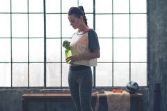 Fit woman standing in profile in loft gym holding water bottle Stock Images