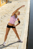 Fit woman stretch body by water pier. Sport young woman stretch body by water pier summer day Stock Photography