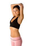 Fit woman stretching. Beautiful fit young woman wearing yoga clothes is stretching before her workout Royalty Free Stock Photo
