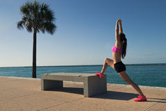 Fit woman stretching along the water Royalty Free Stock Photography